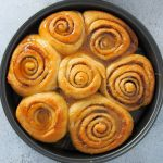 Whole Wheat Cinnamon Rolls with caramel glaze on a round pan.