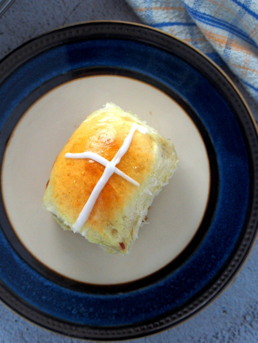 Hot cross bun on a plate.