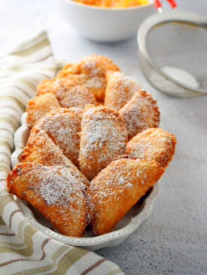 Peach mango pies dusted with powdered sugar, arranged on a serving plate.