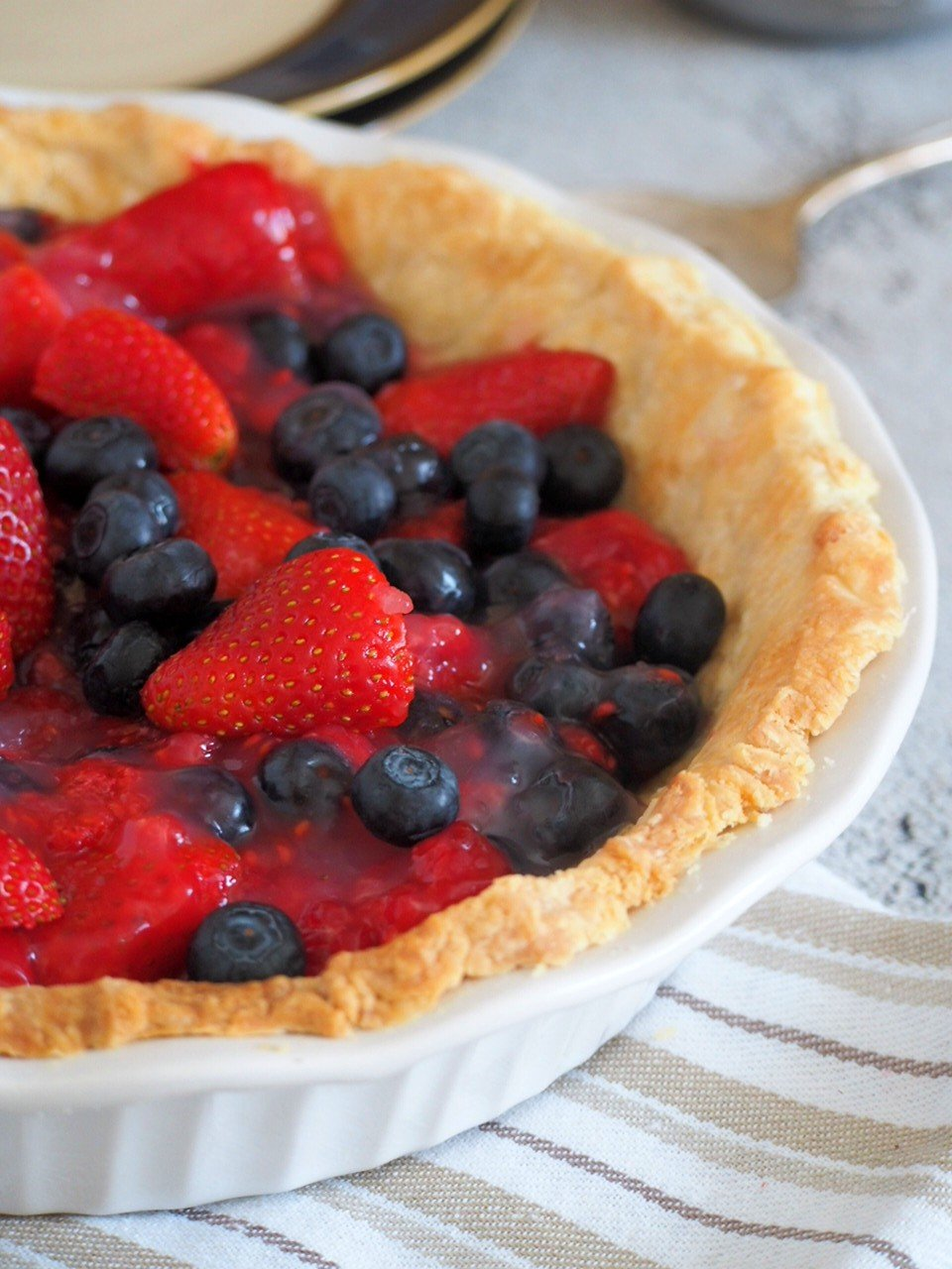 Close up view of glazed triple berry pie.
