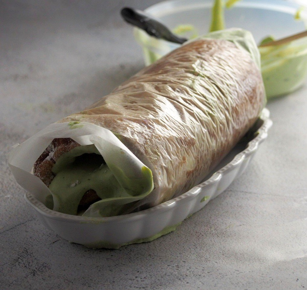 The matcha roll cake right after rolling, still wrapped in parchment paper.