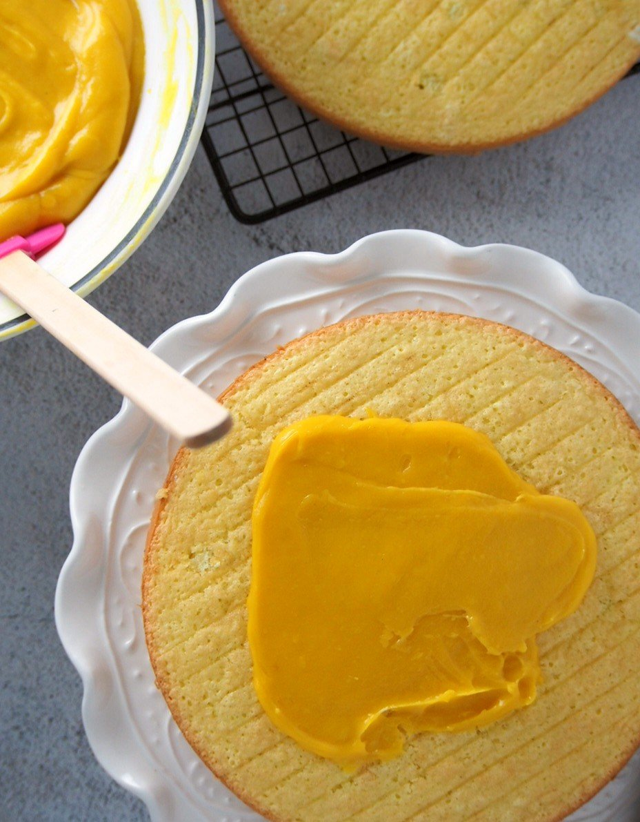 Spreading the mango cream on the sponge layer.