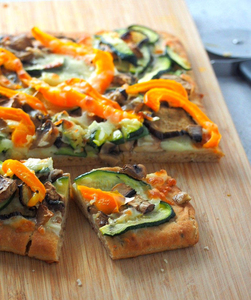 The roasted veggies pizza on a wooden board.
