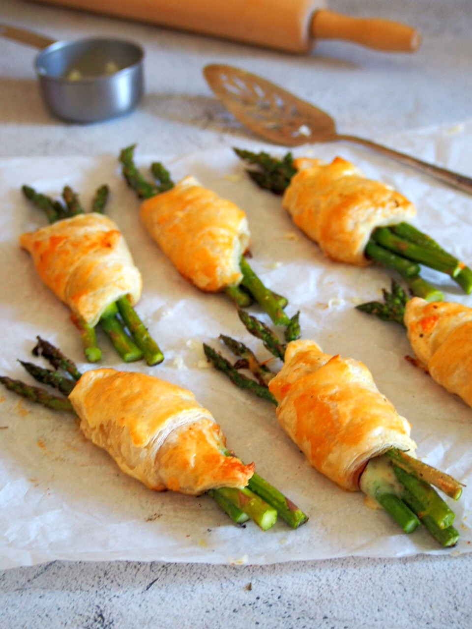 Asparagus and Ham filled puff pastries on a parchment paper.