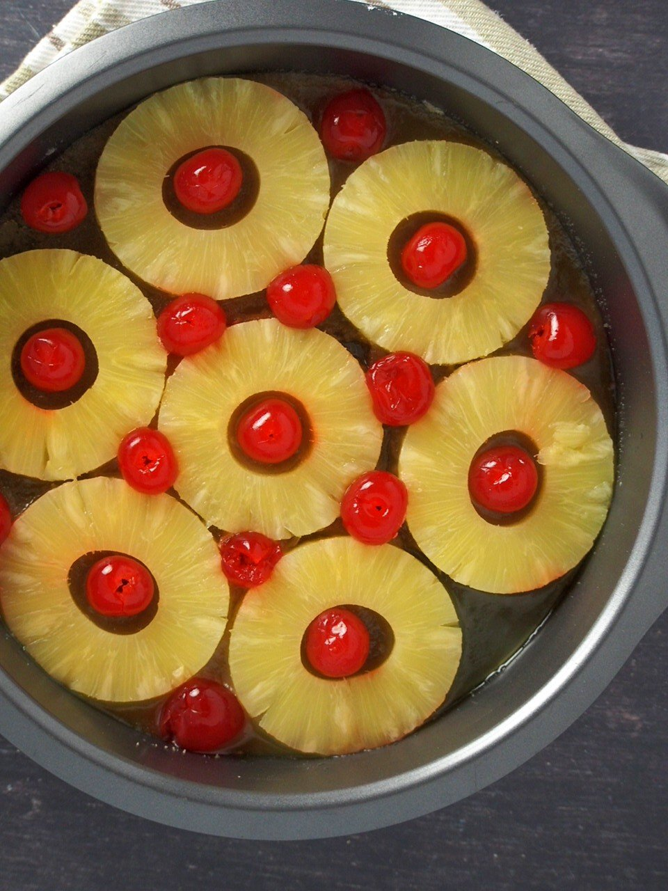 The sliced pineapples and cherries arranged in a single layer in the pan prior to baking.