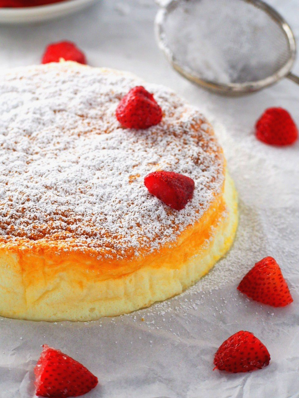 Condensed Milk Cheesecake garnished with icing sugar and strawberries.