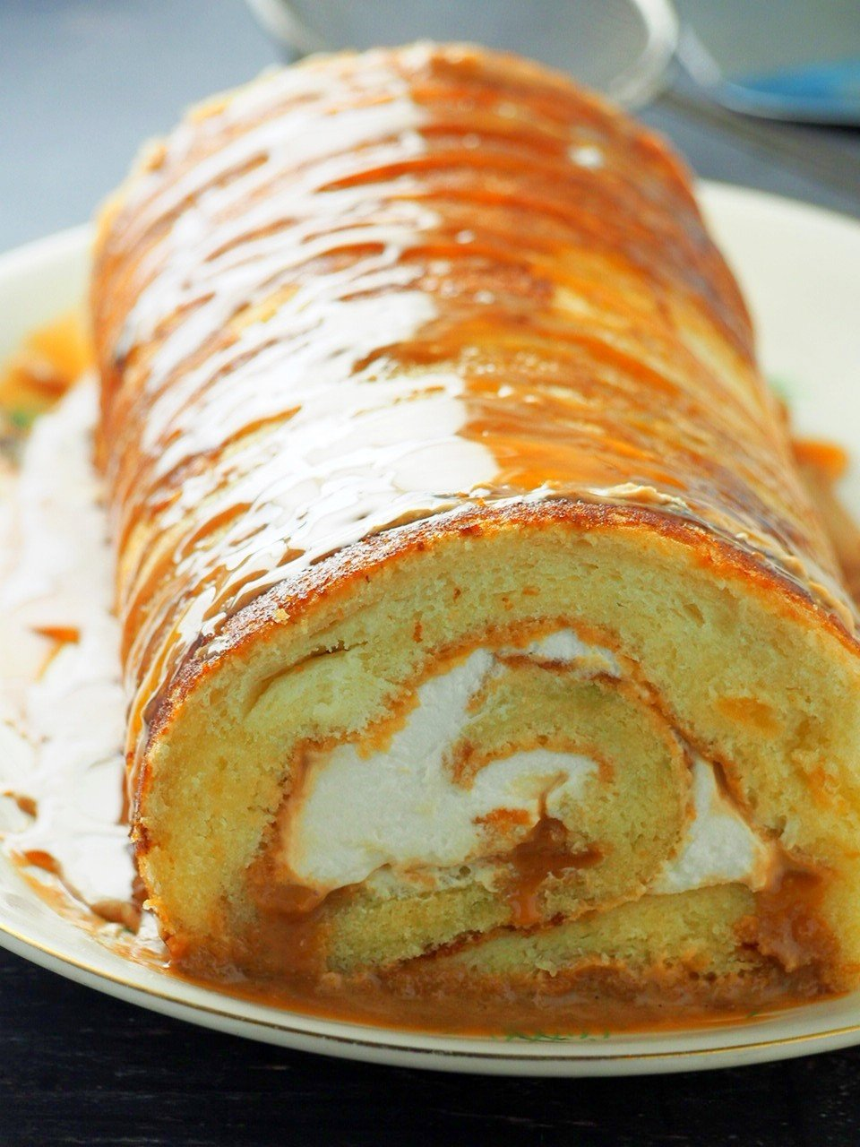 Dulce de leche cake roll on a serving plate.