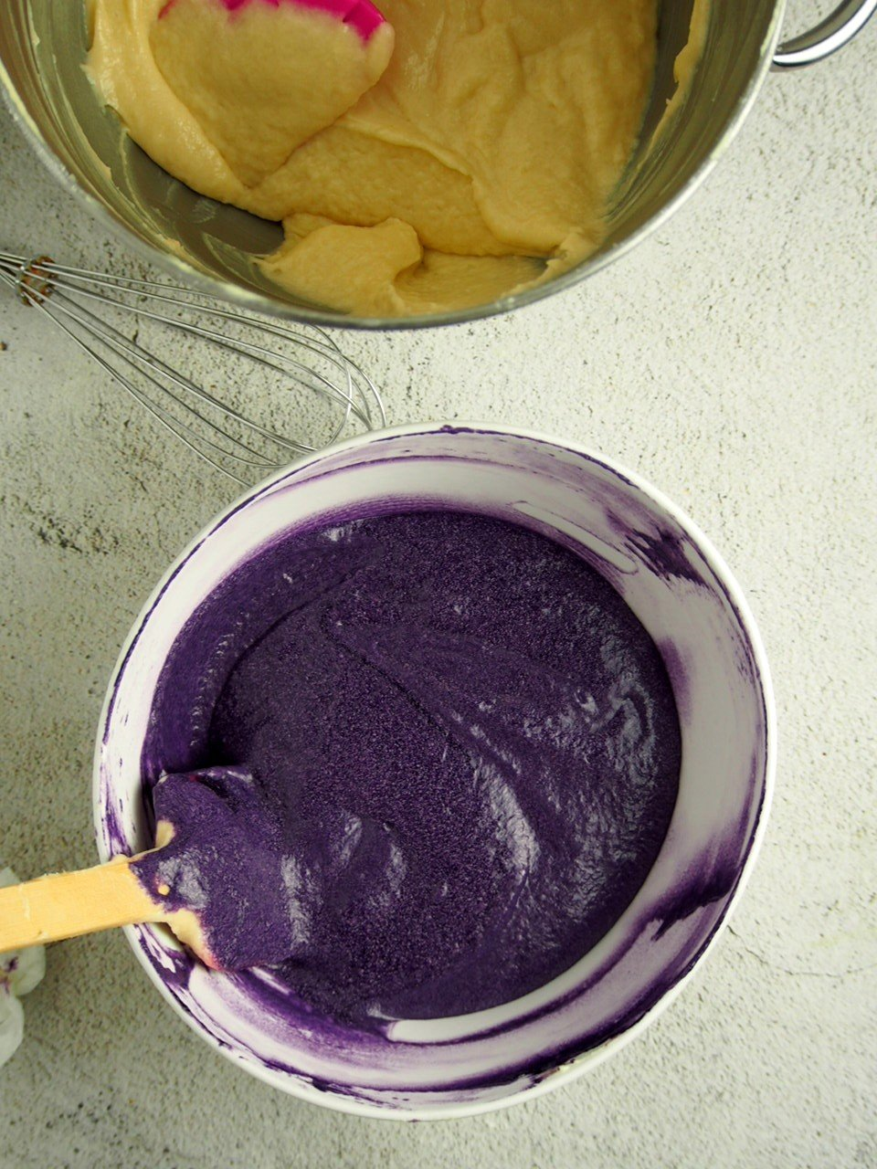 Ube flavored batter and vanilla batter in two bowls.