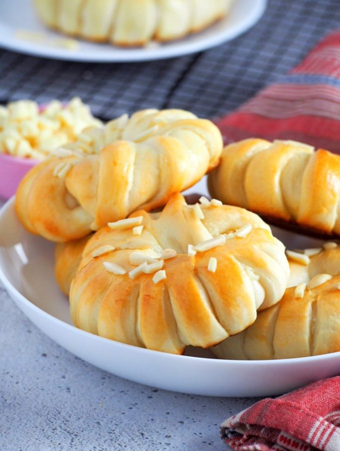 White chocolate buns with almonds on a serving bowl.