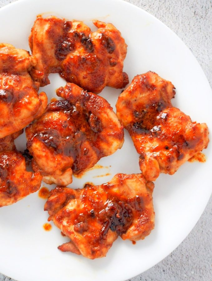 Top shot of saucy baked chicken thighs on a white plate.