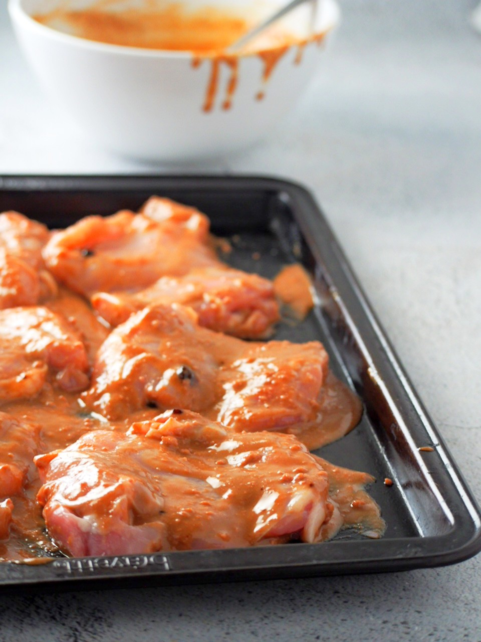 Raw chicken thighs on baking tray, smothered with the liver spread sauce.