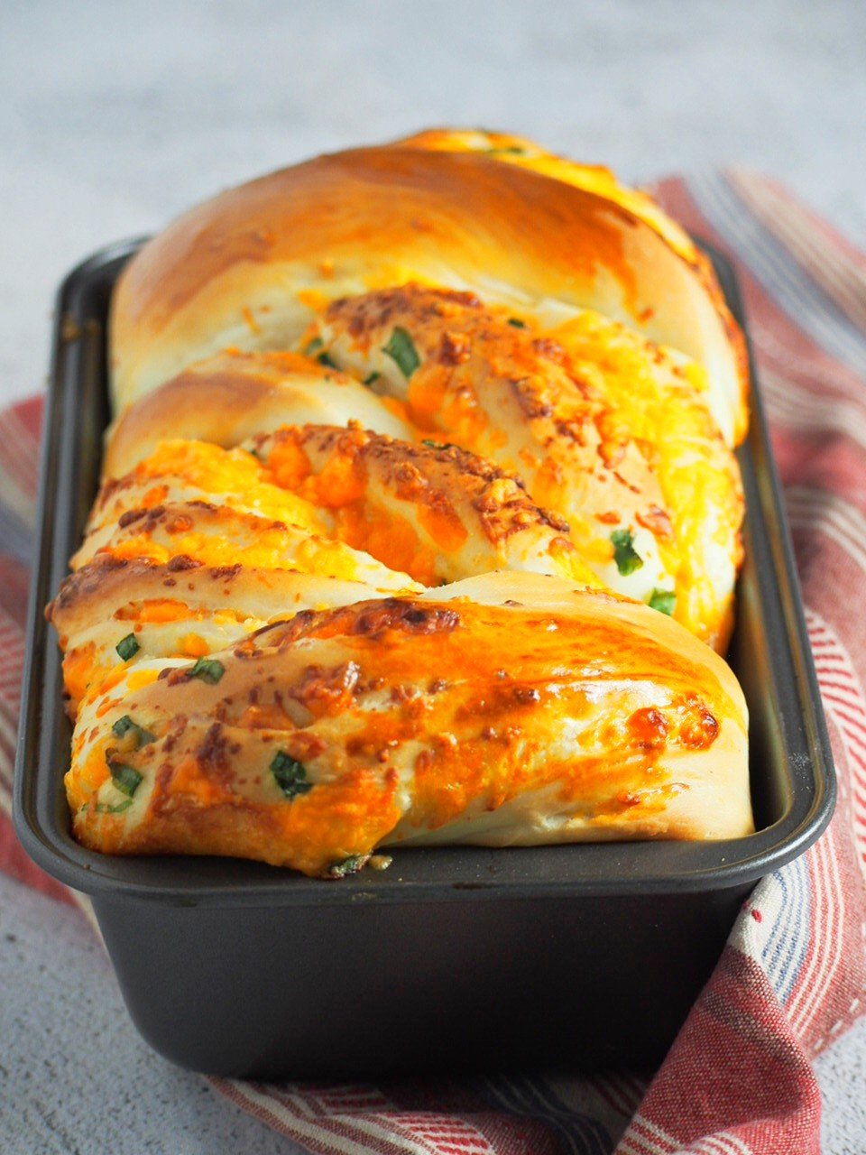 Cheese loaf bread on a loaf pan, freshly baked.