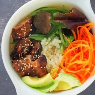 The korean chicken bowl, complete with all the garnishes, on a white bowl.