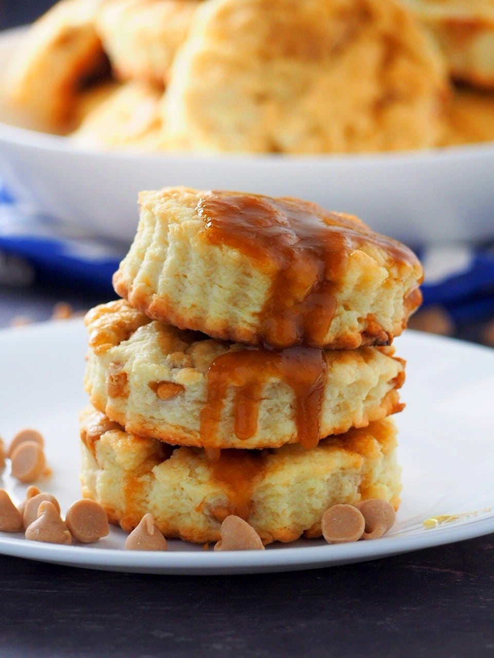 Salted Caramel Scones stacked in a plate and surrounded by caramel chips.