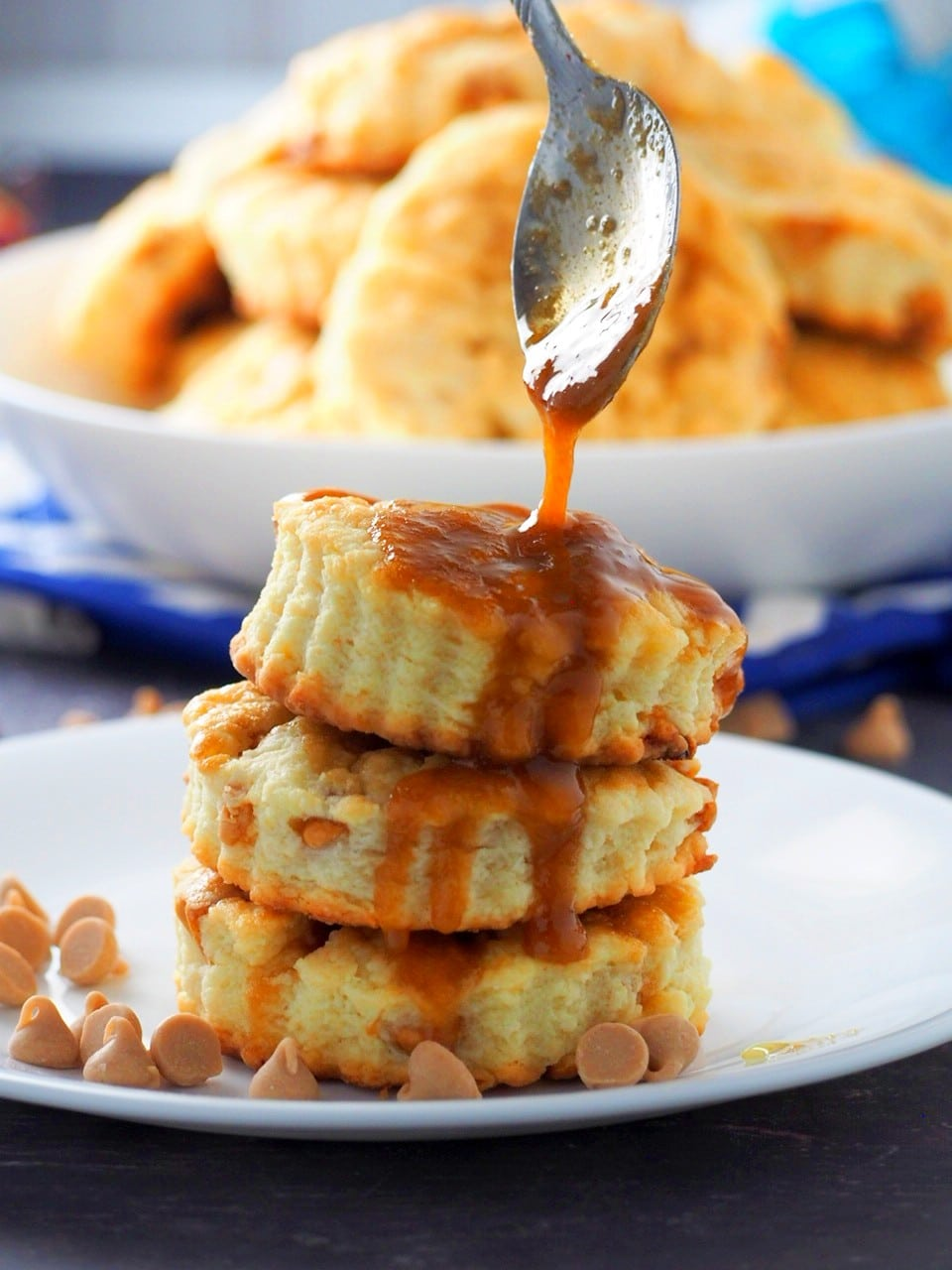 Drizzling caramel sauce on top of the stacked salted caramel scones.