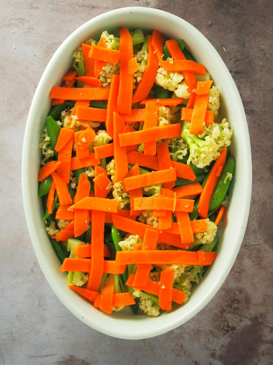 The blanched veggies arranged on a baking dish.