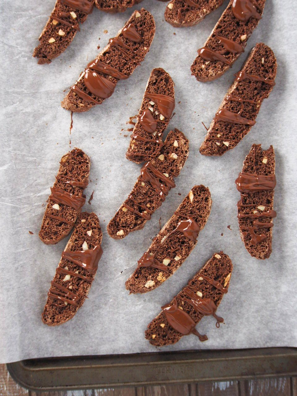 The glazed almond chocolate biscotti on a parchment paper.