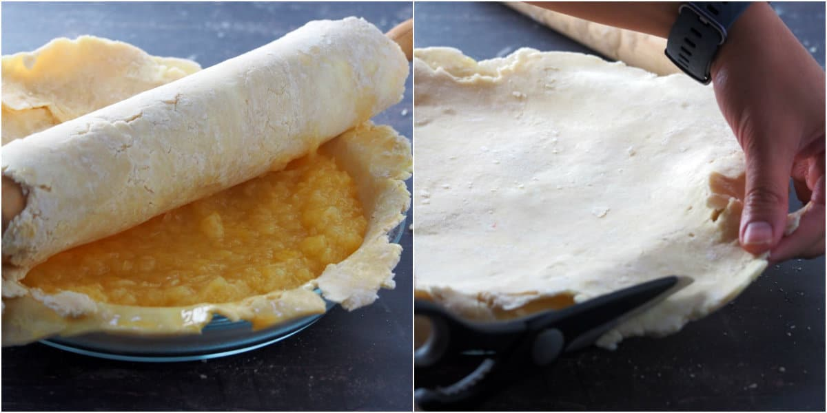 The top pie crust being positioned on the pie plate over the filling.