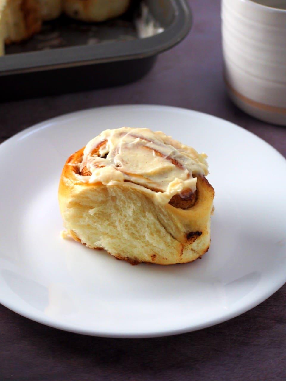 A cinnamon bun on a small plate.