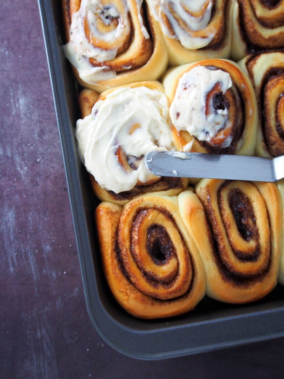 Slathering the cinnamon rolls with cream cheese icing.