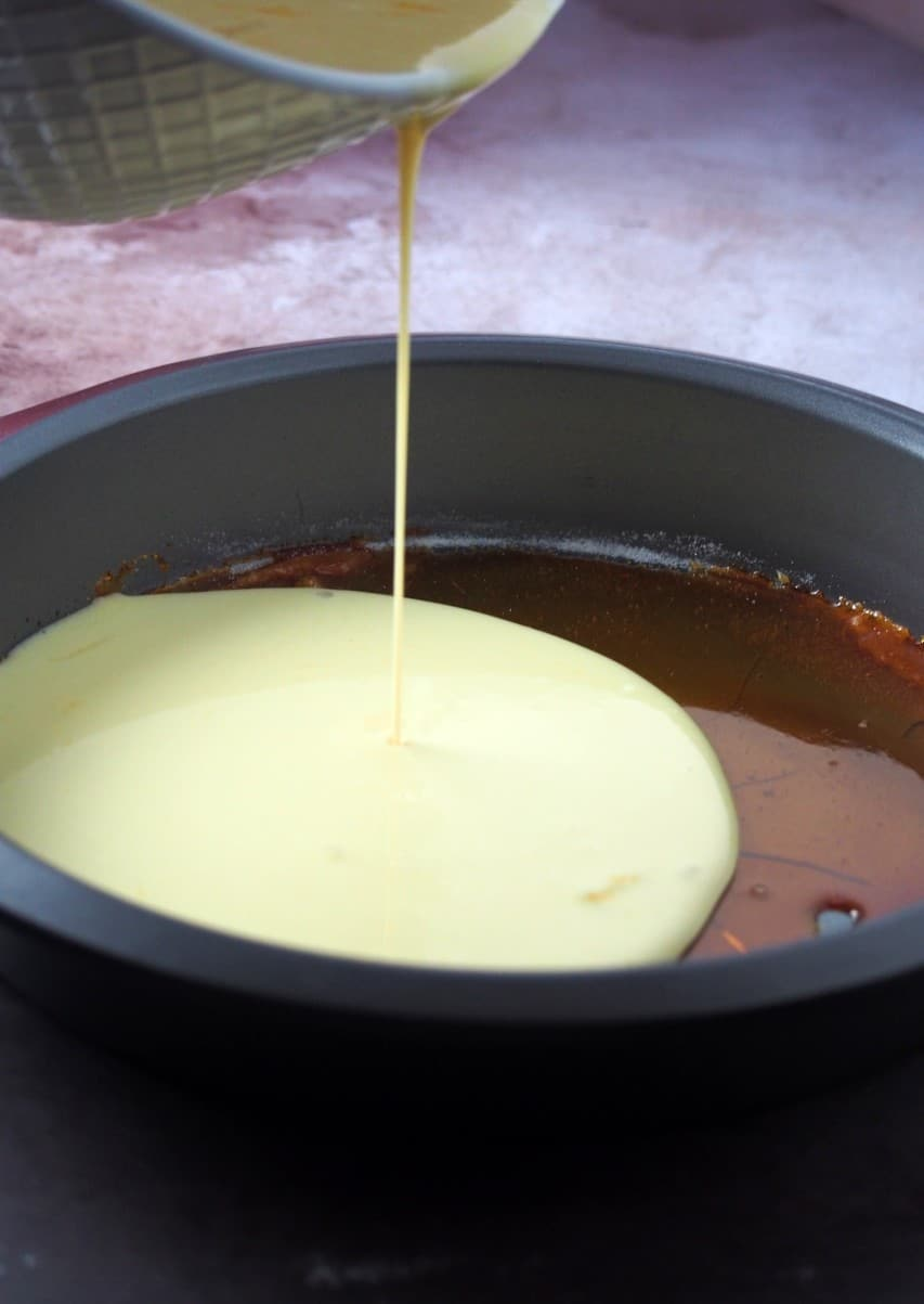 Pouring the custard mixture over the caramelized sugar in the baking pan.