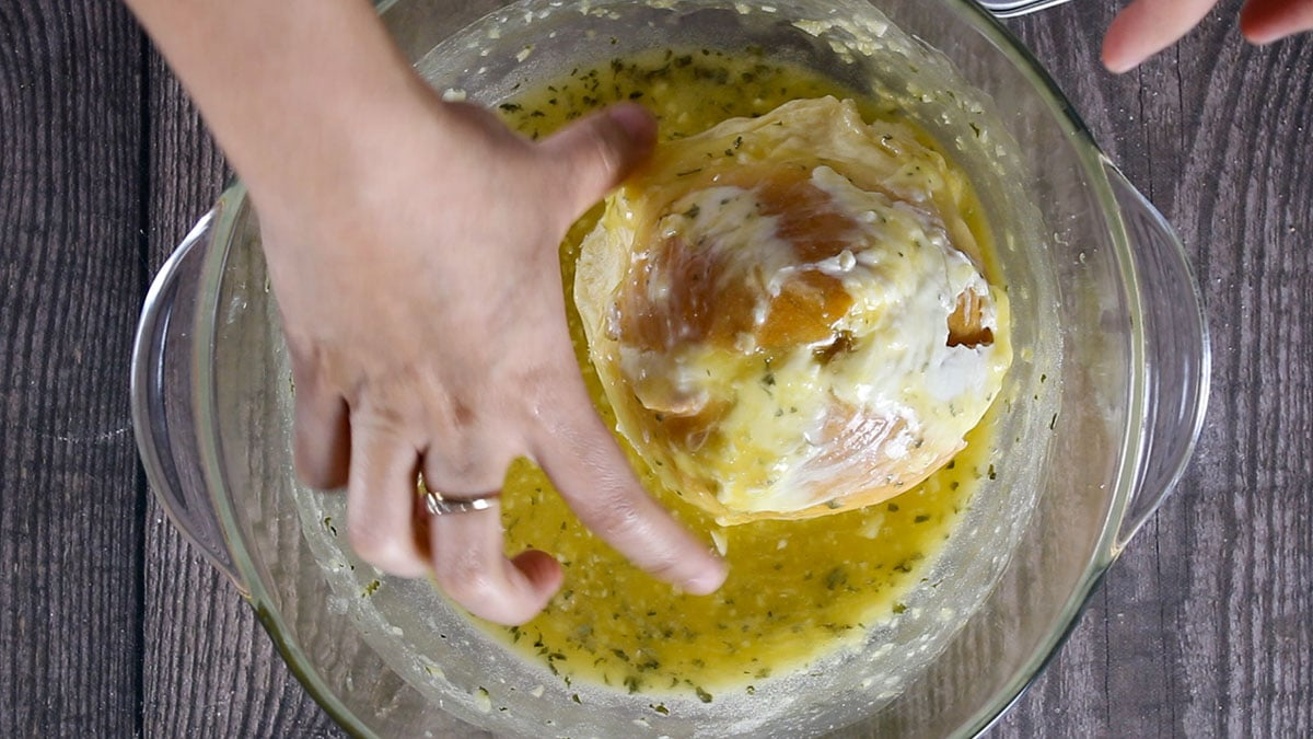 Dipping the bread into the garlic butter sauce.