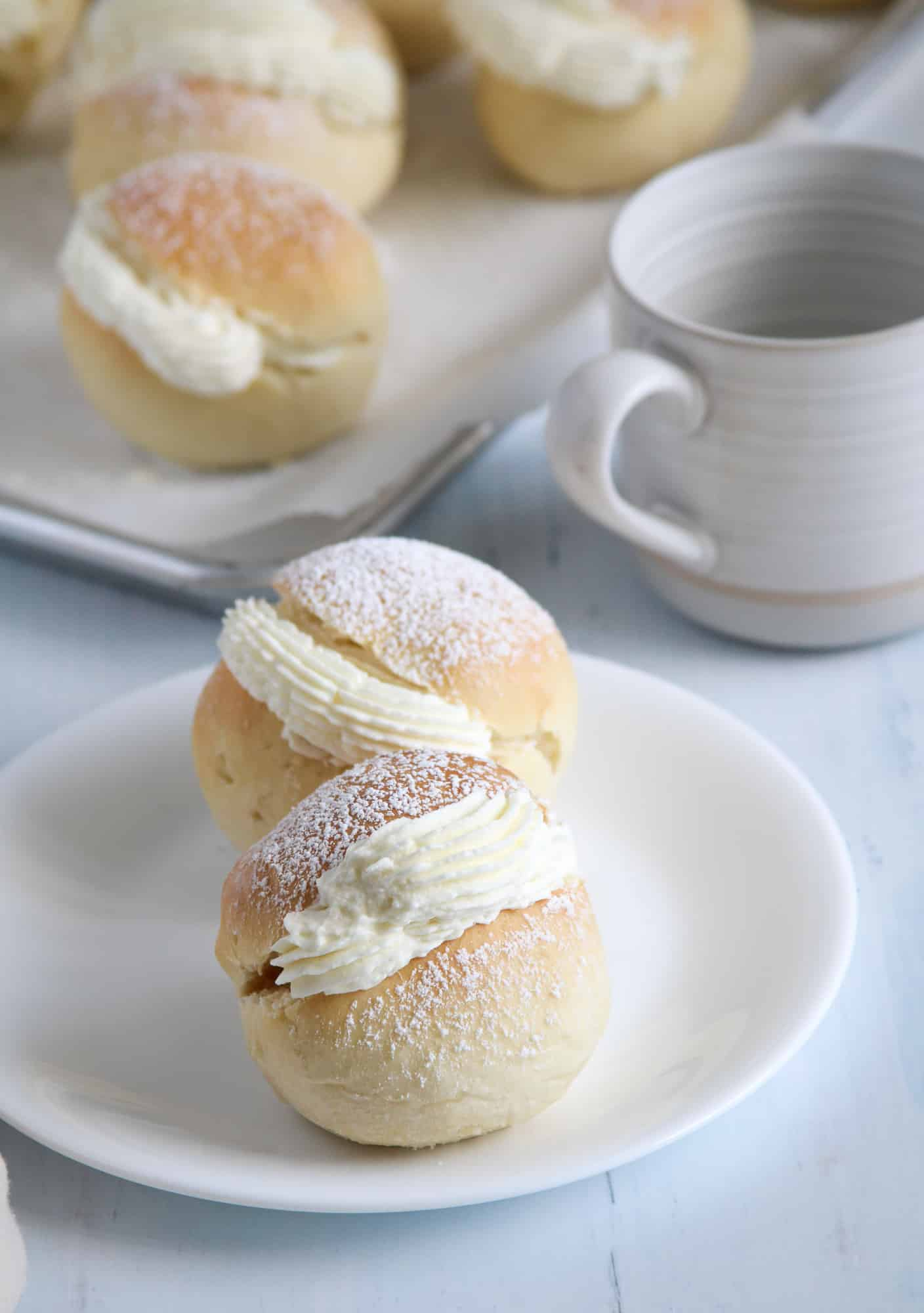 Two cream buns served on a plate.