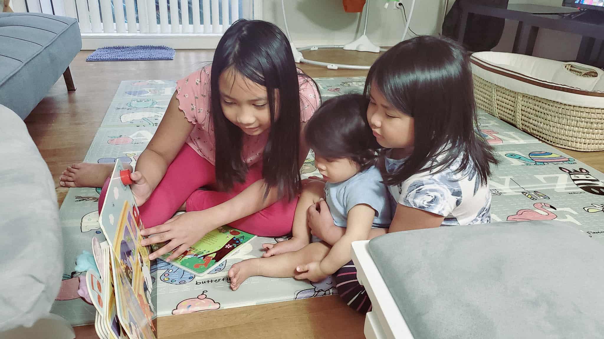 Three kids reading a book.
