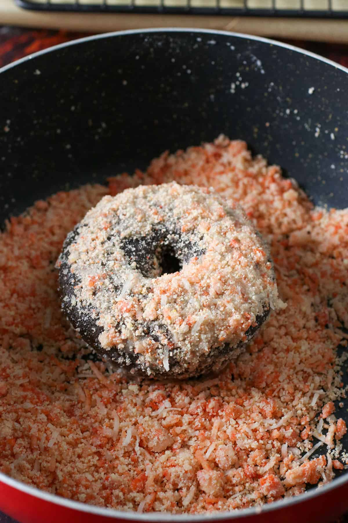 Coating the chocolate donut in butternut streusel.